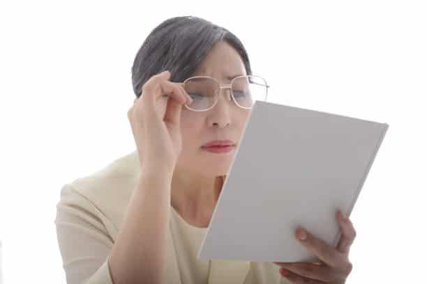 Femme d'une quarantaine d'années qui porte des lunettes pour presbyte pour lire