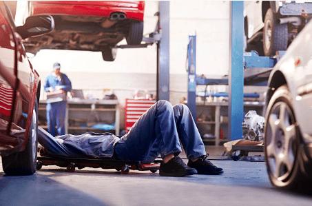personne allongée qui répare une voiture par le dessous