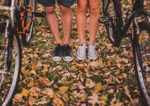 homme et femme dont on ne voit que les jambes à partir du genou portant des converses noires et blanches à côté de vélos sur sol plein de feuilles mortes