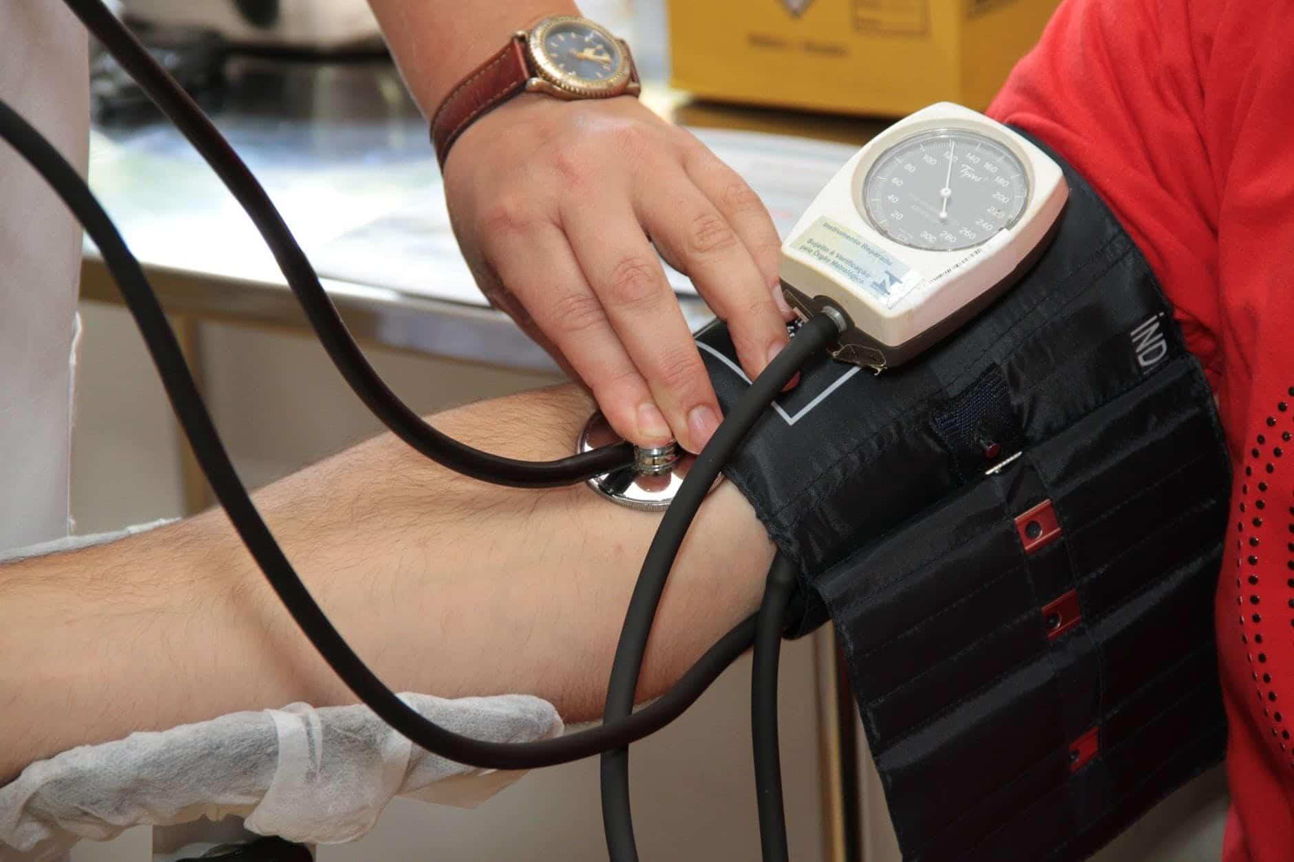 Médecin qui mesure la tension d'un patient avec un tensiomètre manuel
